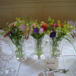Tischdekoration Hochzeit - farbenfrohe Sträuße in Glasvasen