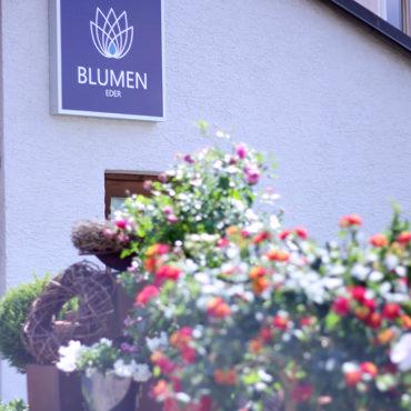 Blumenhaus Eder Firmenlogo an Hauswand