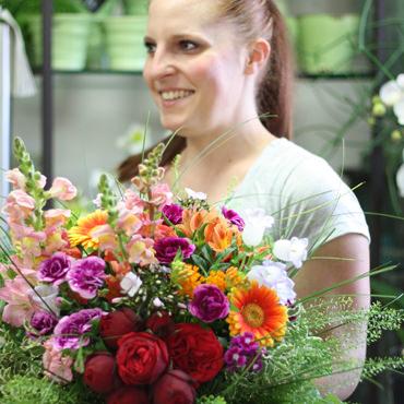 Mitarbeiterin mit farbenfrohem Blumenstrauß in der Hand